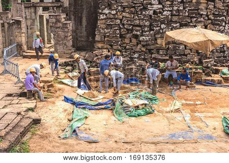 Bayon, Siem Reap, Cambodia - December 7, 2016: Architects And Workers