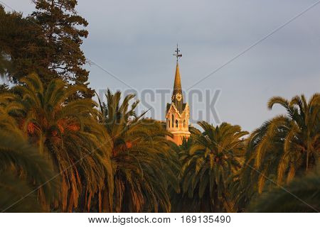 Barcelona Spain - January 03 2017: The tower of Gaudi House Museum between the palm trees at sunset time