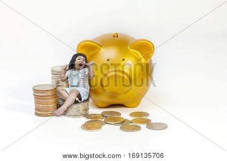 conceptual image happy child little girl sitting on a pile of coins close gold piggy bank.