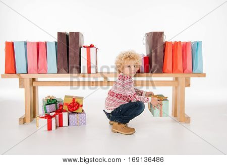Kid sitting with stack of shopping bags and gift boxes around him isolated on white
