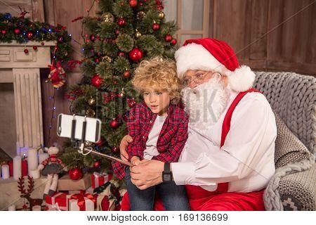 Santa Claus with kid taking selfie near christmass tree