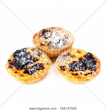 Pastel de Nata - creamy sweet curstard with black crust and sugar powder isolated on white. Pasteis de Belem egg tart