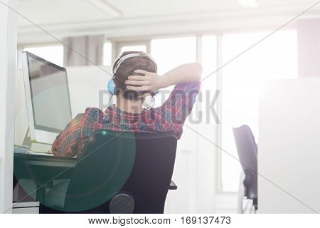 Rear view of young businessman wearing headphones at computer desk in office