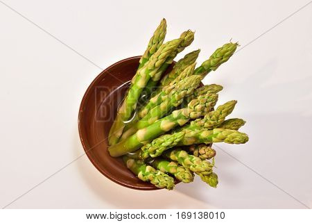 Isolated green asparagus in a ceramic pot. Centered, copy space. healthy. Food. foodphotography. White background Close up. Top view.