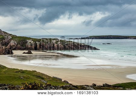 North Coast Scotland - June 6 2012: Durness Beach is a sandy patch looking north on a rough coast among rock cliffs and sprinkled pieces of rock. Under rainy sky with the light blue ocean gently flowing in.