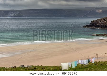 North Coast Scotland - June 6 2012: Line of multi-colored laundry hangs above Durness Beach a sandy patch looking north on a rough coast among rock cliffs and sprinkled pieces of rock.
