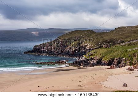 North Coast Scotland - June 6 2012: Cliffs descend on Durness Beach a sandy patch looking north on a rough coast among rock cliffs and sprinkled pieces of rock.