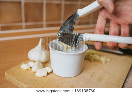 Garlic crushed squeezed from garlic press with white bowl and wooden cutting board.