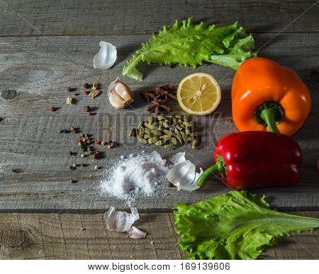 still life with vegetables: carrot pepper lettuce leaves garliclemon rustic stile space for inscriptions.