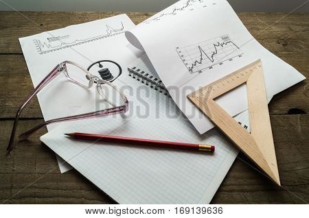 Business concept with note diagramms glasses and pensil.