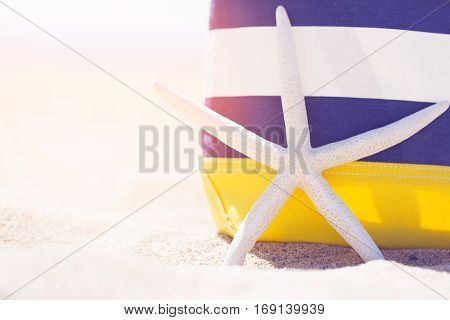 view of colorful beach bag and starfish in the sand with sun flare vacation concept