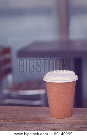 disposable coffee cup at the table in empty cafe