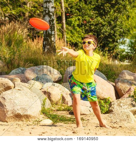 Play and fun concept. Little playful enjoyable boy kid throwing frisbee disc. Male child having fun playing outdoor on beach.