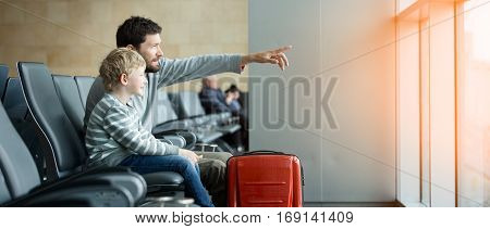 panorama of happy family of two father and son waiting together at the airport for plane departure with luggage father pointing with finger at something sun flare effect