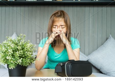 Young woman with virtual reality glasses make her eyes pain. she is rubbing her eyes.
