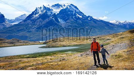 family of two father and son enjoying hiking and active travel in torres del paine national park in patagonia chile view of cuernos del paine