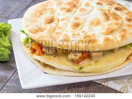 Tender chicken, broccoli and grape tomatoes between provolone slices and pita flat bread spread with Borsin.