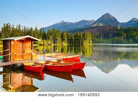 Dreamy boats stand near wooden bridge and a hut on a mountain lake on a spring day.Strbske Pleso lake Slovakia Tatra mountains