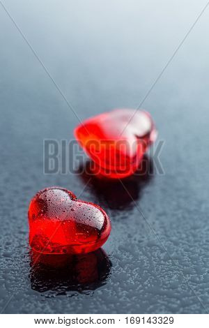 Dewy red hearts on black table.