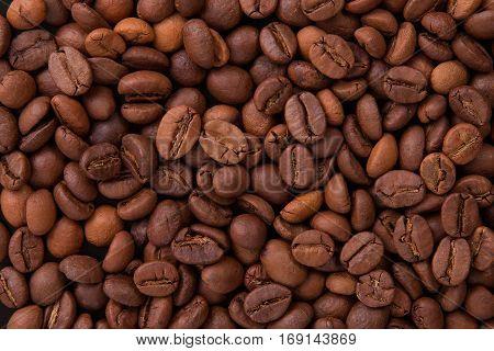 Background of coffee seeds. Roasted coffee closeup