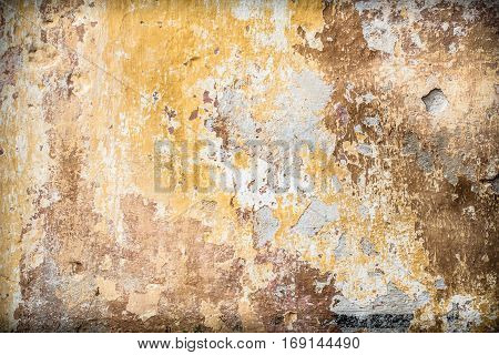 Old vintage rustic wall with cracked paint layers as an aging ruin background