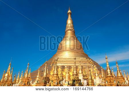 Biggest golden stupa in Shwedagon Zedi Daw (Great Dagon Pagoda, Golden Pagoda), Yangon, Myanmar (Burma). On blue sky background