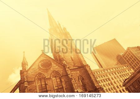 Old church in front of modern glass-and-steek buildings of Boston Downtown vintage look colorized with flare