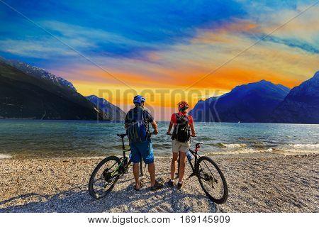 Mountain biking, couple with bikes at sunset on Lake Garda, Riva del Garda, Italy