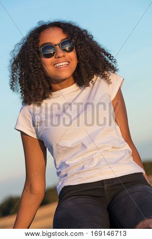 A beautiful and happy mixed race African American female girl child teenager young woman in sunshine wearing sunglasses and smiling with perfect teeth