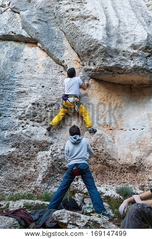 Man climbing on a limestone wall, rock on the background