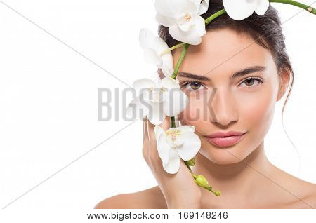 Portrait of beautiful young woman looking at camera with a flower. Close up face of beauty girl holding white orchid flower across her face isolated on white background. Skin care and beauty concept.