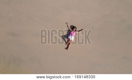 top aerial view of a woman lying on a tropical beach sand