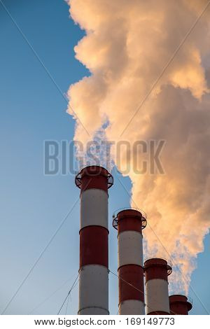 environmental pollution concept, pipes and smog on blue sky background