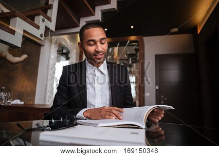 African man in suit sitting with journal in hotel. Below view