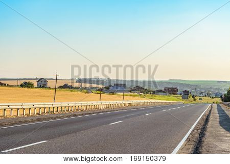 Rural asphalt road with markings and guard rail. Belgorod region Russia.