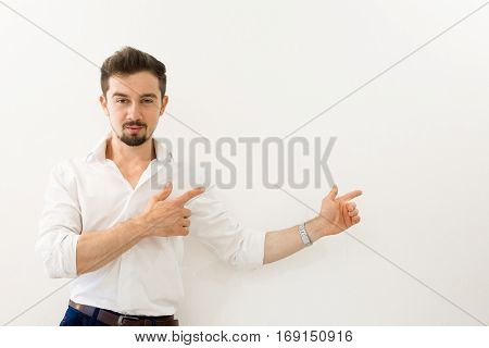 Serious handsome man standing while presenting against white background. Young handsome businessman with beaming smile pointing with finger.