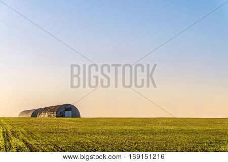 Farm hangars in pure evening field. Agricultural background.