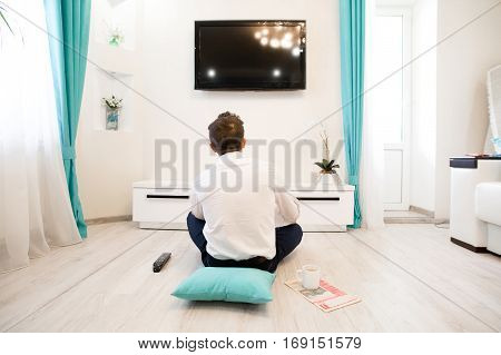 Happy handsome man sitting on the floor and watching television, TV. Young handsome man watching TV on a sofa at home. Man at home sitting in front of tv set.