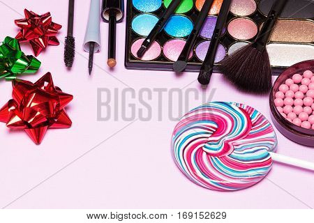 Bright makeup for birthday party. Color glitter eyeshadow, blush, liquid eyeliner, mascara, make up brushes with lollipop and gift wrap bows. Copy space