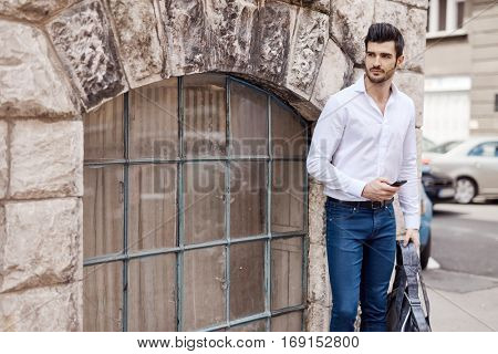 Handsome young man using mobilephone, standing at the corner outdoors.