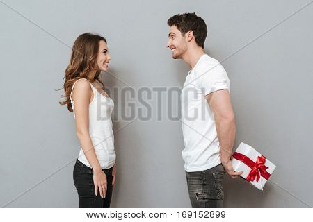 Side view of couple with gift. Man holding gift from the back. Isolated gray background