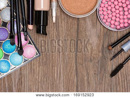 Frame of various makeup products on wooden surface with copy space. Concealer stick, foundation, powder, blush, compact eyeshadow, liquid eyeliner and mascara