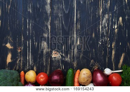 High angle of delicious fresh vegetables forming a half-frame over black background. Home grown products on the edge of the shot