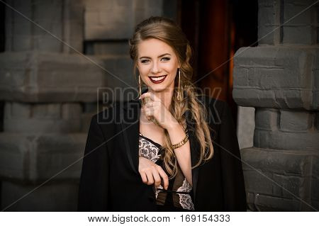Smiling happy cheerful fashionable girl in black dress, jacket on wall stone background. Happiness concept. Picture of pretty stylish smiling girl with beautiful smile. Beautiful smile. Fashion photo.