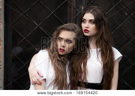 Two scared frightened horror girl in white dressing gown looking aside. Theme Halloween. Dark picture of two beautiful scared hiding girls with opened mouth on black window background.
