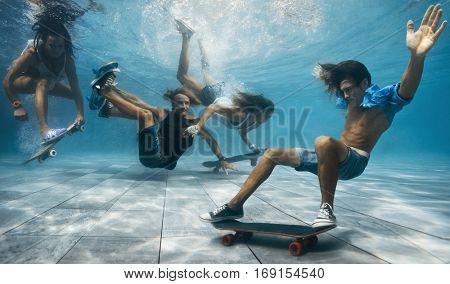 Men and Women skateboarding underwater in the swimming pool