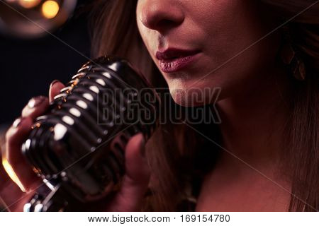 Extreme close-up of woman singing into microphone. Young pretty woman with sexy pink lips singing into silver studio