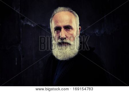 A mid shot of stately handsome man gazing wisely. Man wearing black knitted sweater, turned right