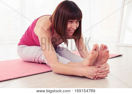 Side view of fitness trainer doing seated forward bend pose on a yoga mat. Sit and straighten legs. Concept exercising workout yoga