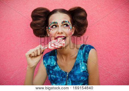 Woman having toothache after eating sweets, lollipop and teeth problem. girl eating sweet candy. caries. Colorful Lollipop in perfect woman teeth and red lips mouth.